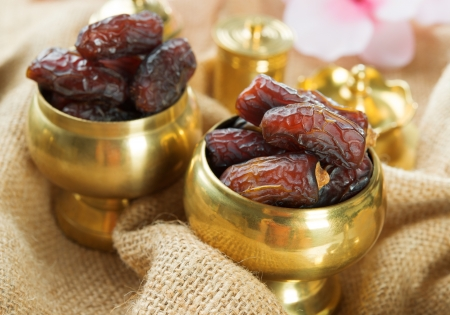 Photo for Dried date palm fruits or kurma, ramadan food which eaten in fasting month. Pile of fresh dried date fruits in golden metal bowl. - Royalty Free Image
