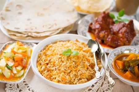 Indian meal biryani rice, chicken curry, masala milk tea, acar vegetable, roti chapatti and papadom.