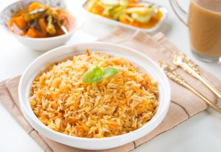 Indian vegetarian food. Biryani rice, curry dhal and milk tea on dining table.