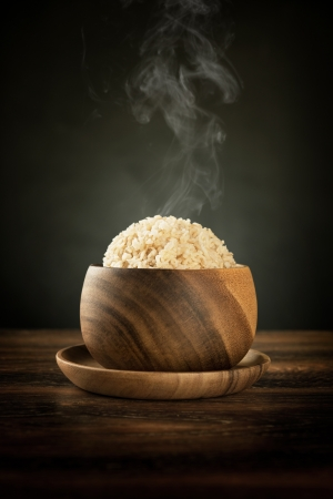 Cooked organic basmati brown rice in wooden bowl with hot steam smoke on dining table. Low light setting.