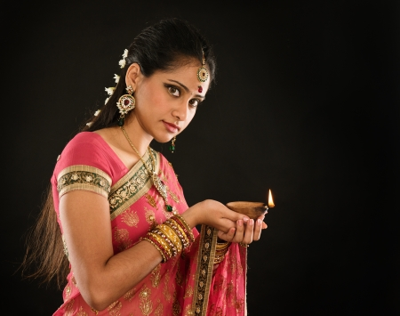 Portrait of beautiful young Indian woman in traditional sari dress holding diwali oil lamp light, isolated on black background.