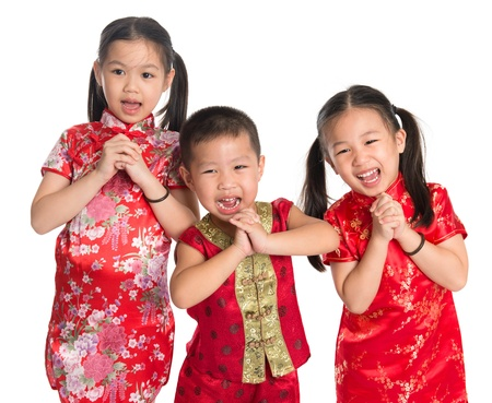 Little oriental children wishing you a happy Chinese New Year, with traditional Cheongsam standing isolated on white background.