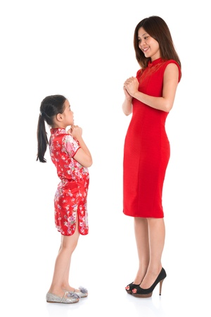 Happy Chinese New Year! Full length Chinese parent and child in traditional Chinese cheongsam greeting to each other, isolated on white background