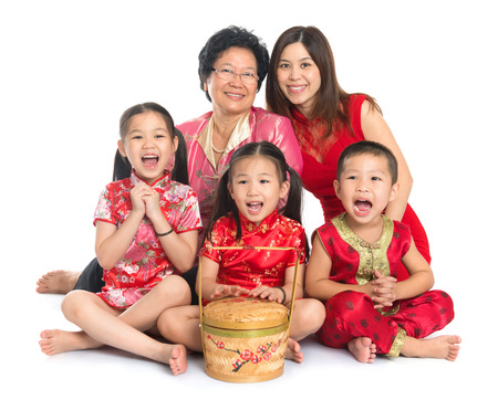 Group of happy multi generations Asian Chinese family wishing you a happy Chinese New Year, with traditional Cheongsam sitting isolated on white background.