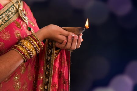 Diwali or deepavali photo with female hands holding oil lamp during festival of light