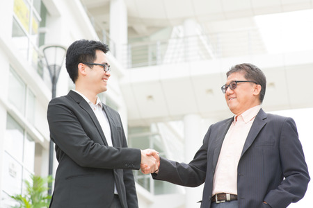 Asian businessmen handshaking. Senior CEO hand shake with young executive.