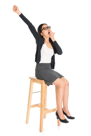 Full body Asian business woman yawning, seated on chair isolated white .