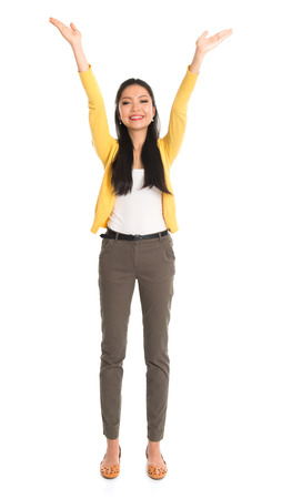Asian girl arms up like holding something above, full length standing isolated on white background.