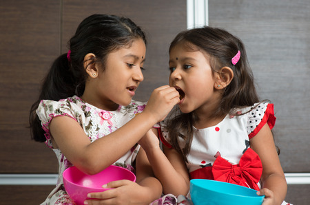 Photo pour Indian girls sharing food, murukku with each other. Asian sibling or children living lifestyle at home. - image libre de droit