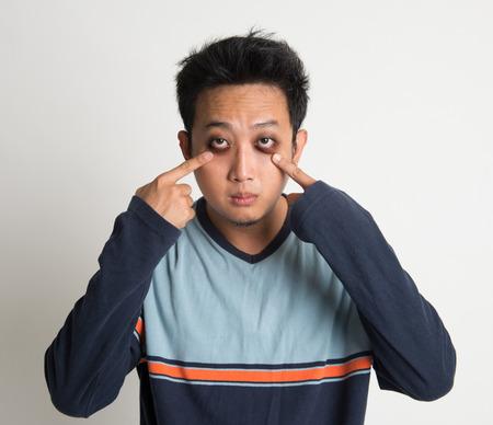 Asian man insomnia, with big eyes bag, on plain background