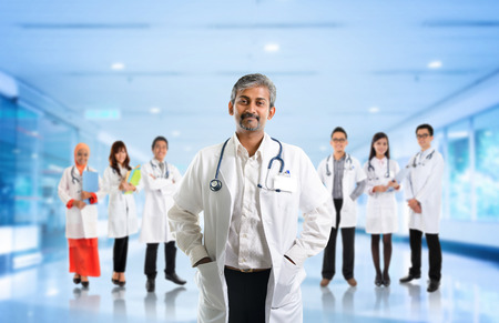 Multiracial diversity Asian medical team, expertise senior and mature doctors leading young practitioners, standing inside hospital.
