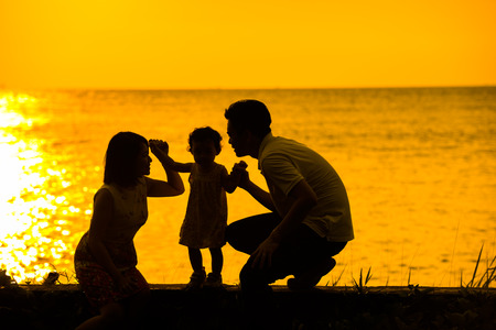 Foto de Silhouette of happy Asian family playing at outdoor beach during summer sunset. - Imagen libre de derechos
