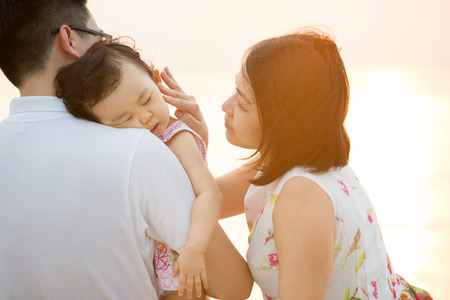 Portrait of lovely Asian family seated on beach outdoor vacation, during summer sunset, natural sunlight with flare.