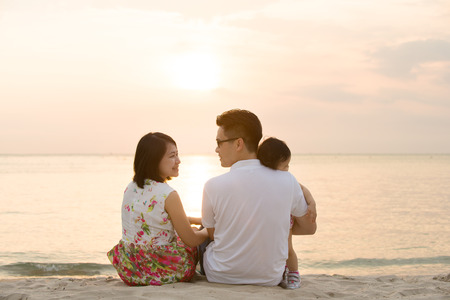 Foto de Portrait of young Asian family seated on beach outdoor vacation, during summer sunset, natural sunlight.  - Imagen libre de derechos