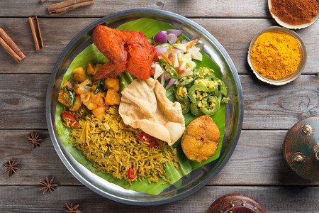 Overhead view of full length Indian biryani rice on wooden dining table background.