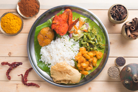 Overhead view of Indian mixed rice on wooden dining table with setting.