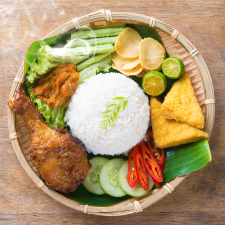 Famous traditional Indonesian food. Delicious nasi ayam penyet with sambal belacan. Fresh hot with steam smoke.の写真素材