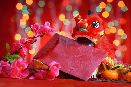 Photo pour Chinese new year festival decorations, miniature dancing lion and ang pow or red packet with copy space ready for text, on glitter red background. - image libre de droit