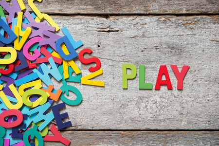 Foto de The colorful words PLAY made with wooden letters next to a pile of other letters over old wooden board. - Imagen libre de derechos