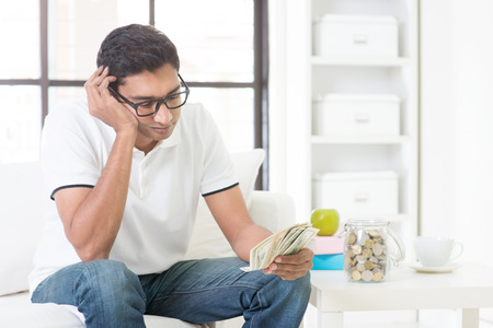 Financial problems concept. Indian guy counting money with sad expression, sitting on sofa at home. Asian male indoor portrait.