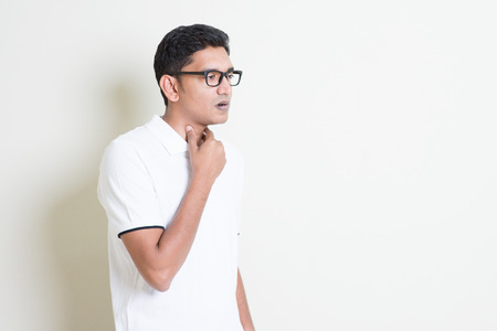 Portrait of Indian guy sore throat, hand on neck clearing throat. Asian man standing on plain background with shadow and copy space. Handsome male model.