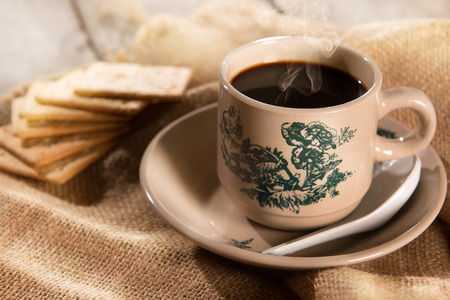 Steaming traditional oriental Chinese kopitiam style dark coffee in vintage mug and saucer with soda crackers. Fractal on the cup is generic print. Soft focus setting with dramatic ambient light on dark wooden background.