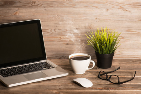 Photo pour Wooden workplace with laptop, cup of hot coffee, mouse, glasses and pot plant, in dramatic light vintage toned. - image libre de droit