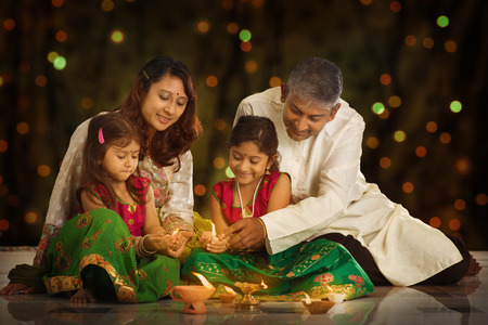 Photo for Indian family in traditional sari lighting oil lamp and celebrating Diwali or deepavali, fesitval of lights at home. Little girl hands holding oil lamp indoors. - Royalty Free Image