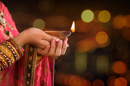 Close up Indian woman in traditional sari lighting oil lamp and celebrating Diwali or deepavali, fesitval of lights at temple. Female hands holding oil lamp, beautiful lights bokeh background.
