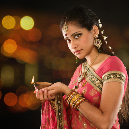 Foto de Indian girl in traditional sari lighting oil lamp and celebrating Diwali or deepavali, fesitval of lights at temple. Female hands holding oil lamp, beautiful lights bokeh background. - Imagen libre de derechos