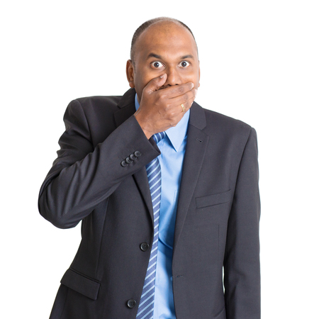 Portrait of shocked mature Indian businessman covered mouth, standing on plain background with shadow.