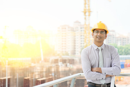 Portrait of Asian Indian male site contractor engineer with hard hat holding blue print paper smiling at construction site, crane with golden sunlight at the background.