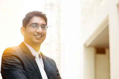 Portrait of Asian Indian business man smiling, outside modern office building block, beautiful golden sunlight at background.