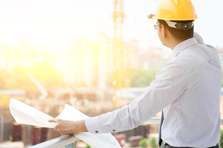 Photo pour Asian Indian male site contractor engineer with hard hat holding blue print paper looking away inspecting progress at construction site, crane with golden sunlight at the background. - image libre de droit
