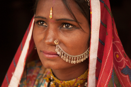 Close up portrait of thoughtful traditional Indian woman in sari dress, India people.