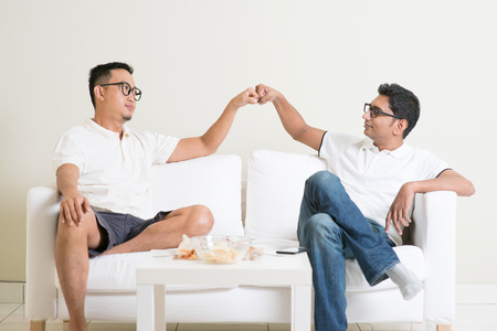Man sitting on sofa and giving fist bump to friend at home. Multiracial people friendship.