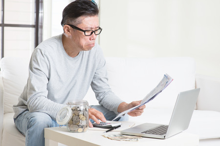 Worried 50s mature Asian man looking at the bills. Saving, retirement, retirees financial planning concept.