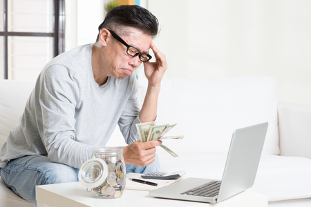 Photo pour Financial problem concept. Portrait of 50s mature Asian man counting money with worried expression, sitting on sofa at home. - image libre de droit