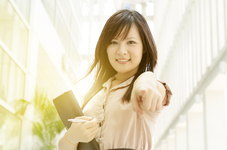 Photo pour Young Asian business woman smiling and pointing at you, standing in an office environment, natural golden sun light at background. - image libre de droit