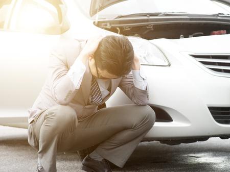 Worried Asian business man squatting beside his breakdown car, feel helpless.