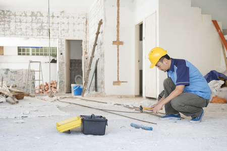 Photo for Construction worker with hardhat working at site, house renovation. - Royalty Free Image