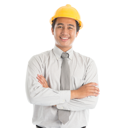 Photo pour Portrait of attractive Southeast Asian engineer with yellow hard hat arms crossed smiling, standing isolated on white background. - image libre de droit