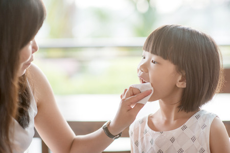 Photo pour Mom wipes mouth for her child at cafe. Asian family outdoor lifestyle with natural light. - image libre de droit