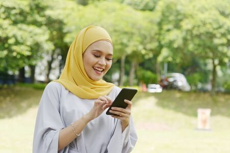 Photo pour Portrait of cheerful Muslim girl using smartphone, smiling at outdoor. - image libre de droit