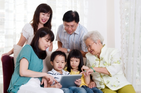 Asian three generations family having fun with tablet computer