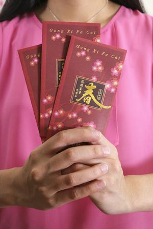 Holding Chinese New Year angpow money envelopes