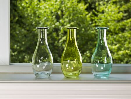 Open window with three vases on sill with green trees in background