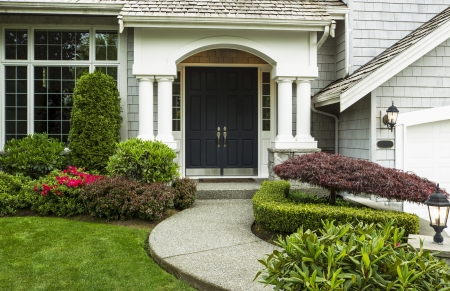 Front Door to home surrounded by seasonal plants and part yard and sidewalk in forefront
