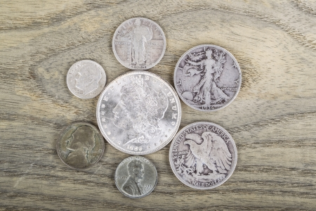 Old Silver Coins on faded white ash wood background