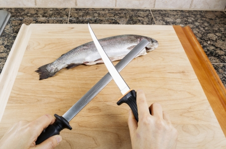 Female hand sharpening fillet knife with single fish on cutting board